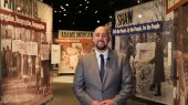 A museum curator stands in front of a colorful exhibit devoted to Washington DC history